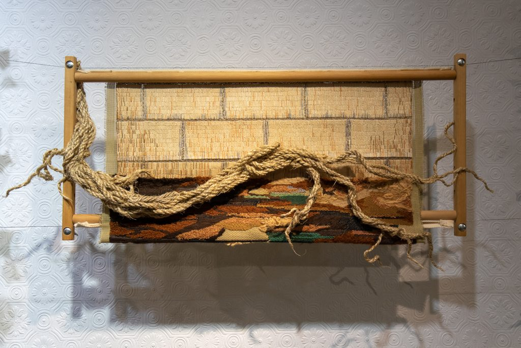 An artwork about inequality made in beige and brown colours, embroidered bricks and tree roots made of ropes